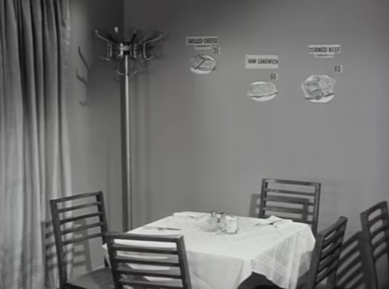 Table and chairs with cut-out pictures of sandwiches on the wall