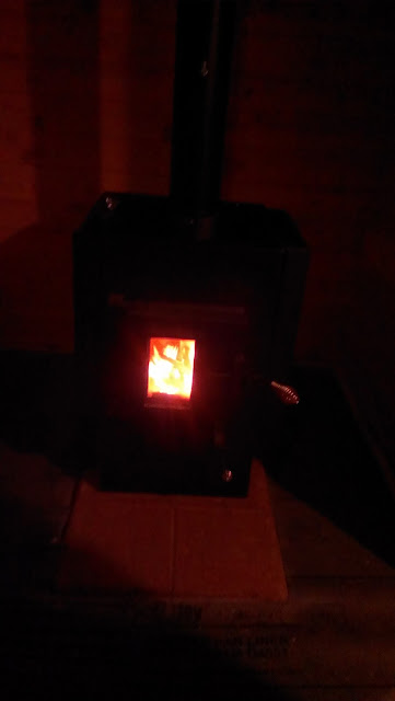 Wood burning Kuuma sauna stove with the lights turned off.