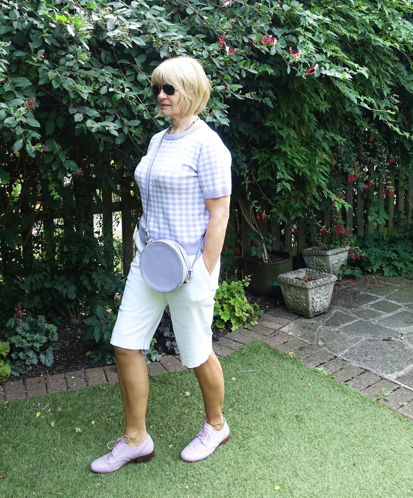 A popular outfit this summer for over 50s blogger Is This Mutton:  lilac check top, white shorts and lilac bag and brogue shoes