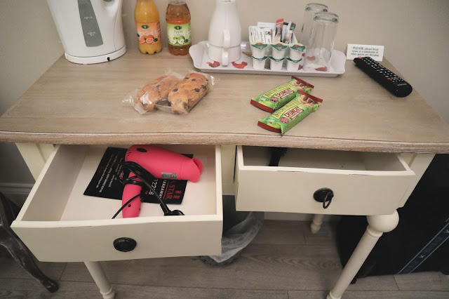 Hillcroft hotel dressing table, with kettle and various breakfast items on the top and a hair dryer in one of the open drawers.