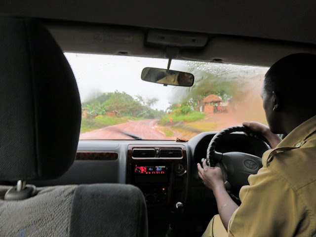Geoffrey Katende, our Matoke Tours guide driving on a red dirt road in Uganda