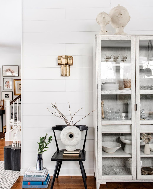 white sculptural modern donut vase sitting on top of chair next to display cabinet
