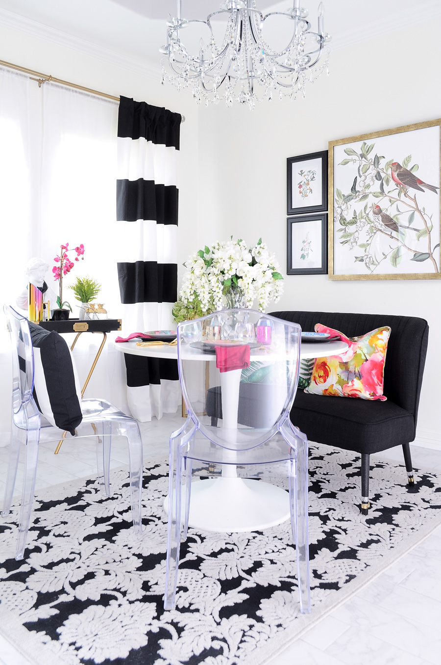 Black and white curtains adorn a colorful and eclectic small dining room space with ghost chairs, florals, and a campaign bar stand.