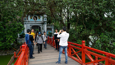 Walking across The Huc bridge to get to Ngoc Son temple