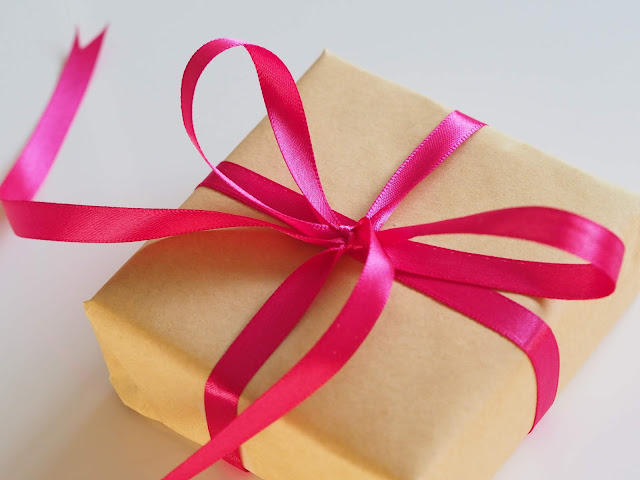 A gift wrapped in brown paper with a pink ribbon