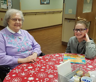 an older woman and a young girl sitting at a table smile for the camera.  A book is on the table in front of them.