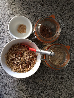 Un bol de flocons d'avoines aux amandes accompagné de deux bocaux en verre avec les ingrédients amande et flocons d'avoine sur plan de travail en granit vue du dessus
