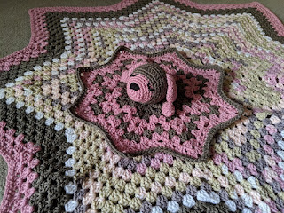 Crochet puppy lovey in pink and brown laying on a crochet star blanket.