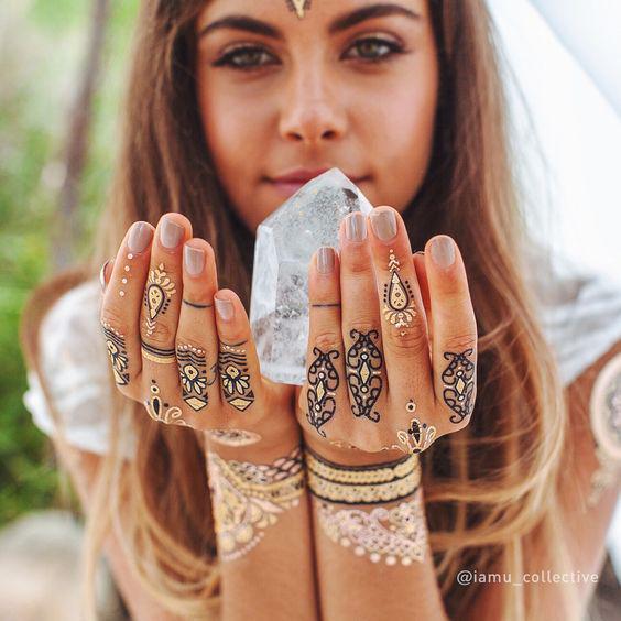 Vemos a chica joven sosteniendo un diamante con ambas manos, lleva tatuajes en los dedos