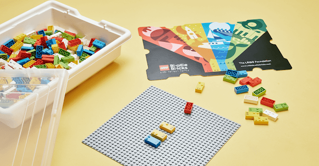 A plastic crate of LEGO Braille Bricks, the paper cover and a LEGO baseplate with some Braille Bricks attached.