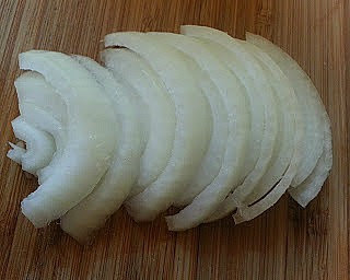 Onions sliced in a row on a chopping board