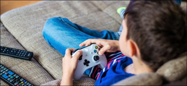 طفل يحمل جهاز تحكم Xbox One