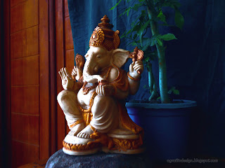 Right View Lord Ganesha Mini Statue On The Stone With Tiny Decorative Flower Plants In The Room
