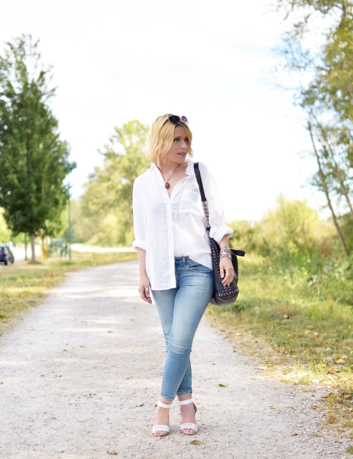 Monika Faulkner styles a white linen shirt with skinny jeans, block-heeled sandals, and an MK bag