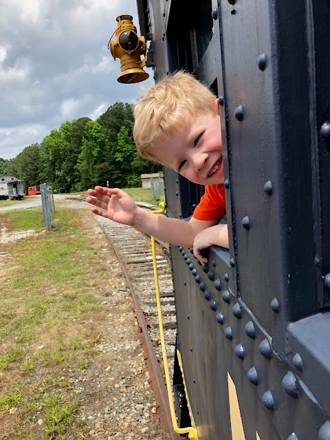 Kid waving out the window of train at the Southeastern Railway Museum