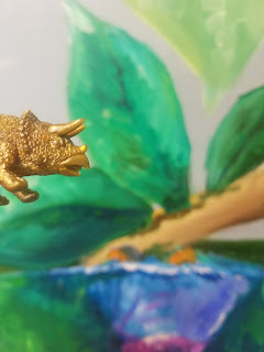 toy triceratops near leaf painting