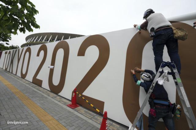 Японские рабочие вешают постер Токио-2020 к Олимпийским играм