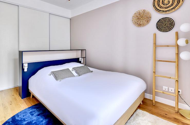Dormitorio con gran armario empotrado detrás del cabecero de la cama.