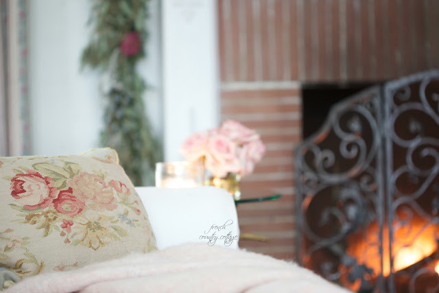 Living room sofa with fire glowing in the background and flowers