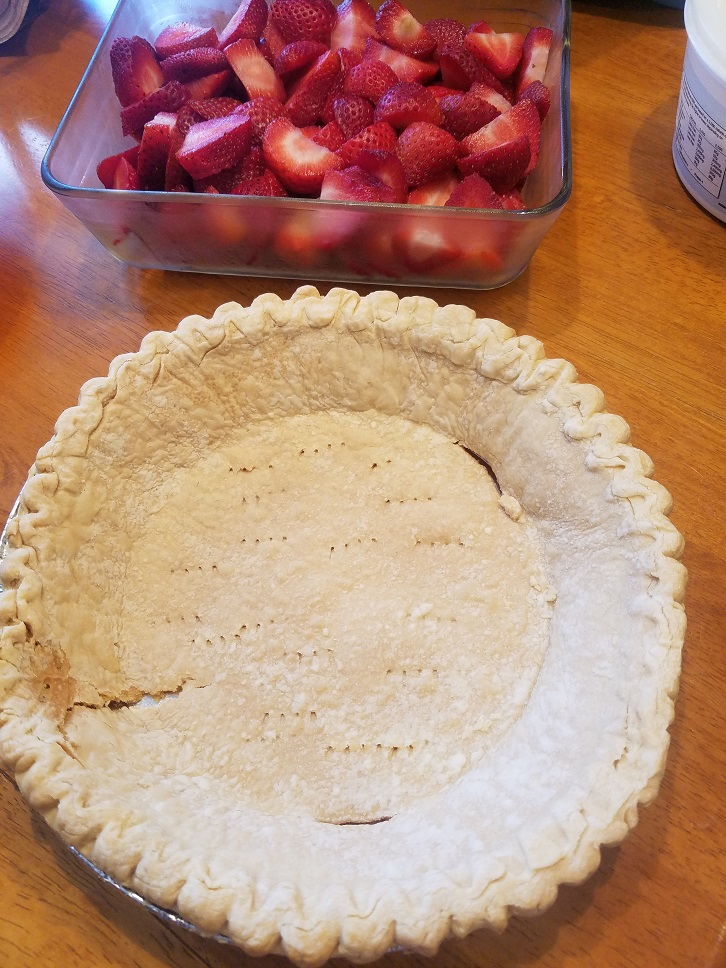 there are sliced strawberries in a glass dish and a baked pie crust with little holes in the crust to prevent it from puffing up during bake times