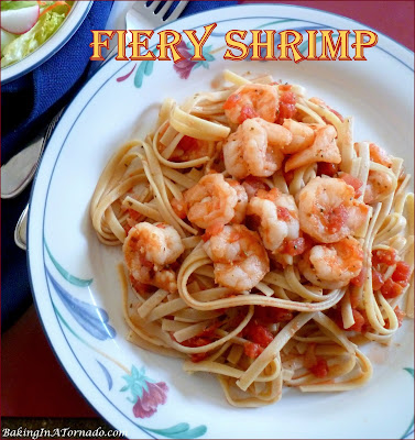 Fiery Shrimp, pan sautéed, steeped in a spicy tomato sauce and tossed with fettuccine. How hot will you go? | Recipe developed by www.BakingInATornado.com | #recipe #dinner