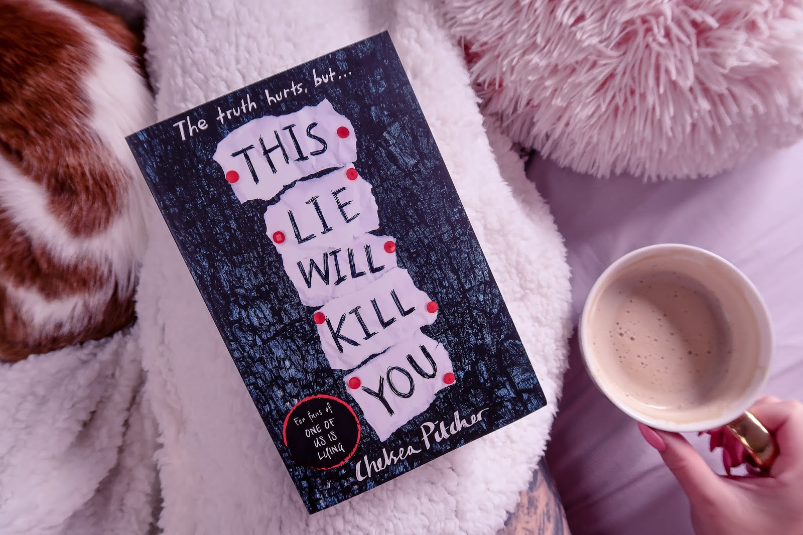 Birds eye view but closer up angle of the book This Lie Will Kill You by Chelsea Pitcher on a white blanket and a cat in the background and pink pillow out of focus with ofaglasgowgirl holding a mug