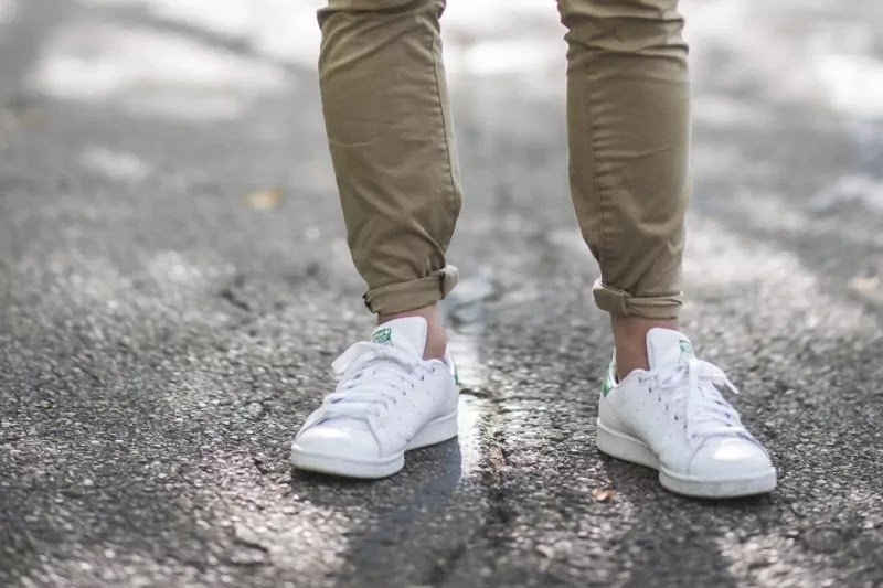 A guy wearing a jeans by rolling its cuff.