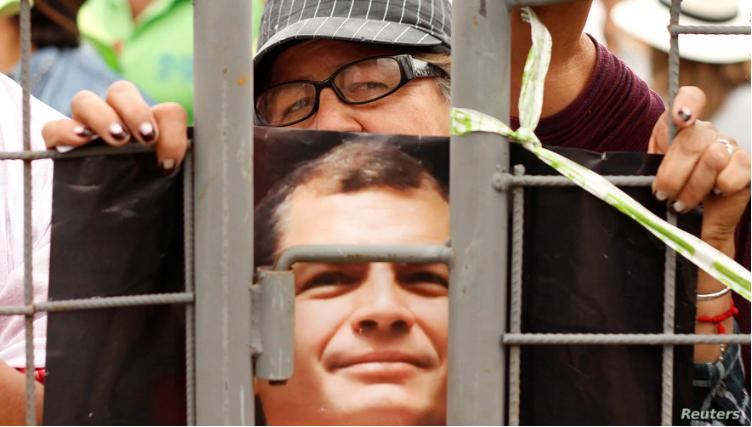 Un seguidor del expresidente Rafael Correa sostiene una imagen del mandatario mientras aguardan a que abandone el país rumbo a Bélgica, el 10 de julio de 2017 / REUTERS