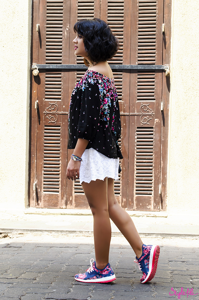 Style File blogger Dayle Pereira showcases her womens fashion outfit with a cold shoulders floral blouse, cutwork shorts, printed sneakers, mini bag and a wavy long bob with coral lips and blue nails