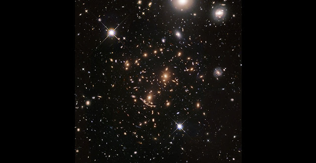 "The galaxy cluster Abell 370 was the first target of the BUFFALO survey, which aims to search for some of the first galaxies in the Universe.  This remarkable cluster in the constellation of Cetus is located approximately four billion light-years away. Its mass, consisting of both hundreds of galaxies and dark matter, bends and distorts the light coming from even more distant objects behind it. This effect is known as strong gravitational lensing.  The most stunning demonstration of gravitational lensing can be seen just below the centre of the image. Nicknamed ""the Dragon"", this extended feature is made up of a multitude of duplicated images of a spiral galaxy in the background of Abell 370 — all lying five billion light-years away.  Credit: NASA, ESA, A. Koekemoer, M. Jauzac, C. Steinhardt, and the BUFFALO team"