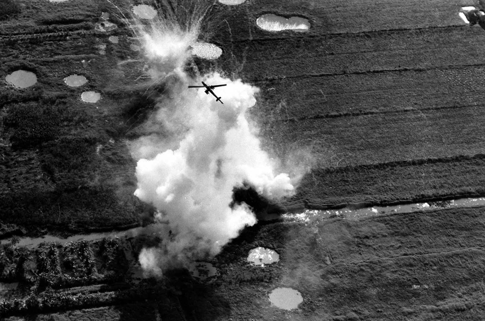 A Cobra helicopter gunship pulls out of a rocket and strafing attack on a Viet Cong position near Cao Lanh in the Mekong Delta on January 22, 1969. Large craters caused by air and artillery strikes brought in on the area can be seen near the white explosion.