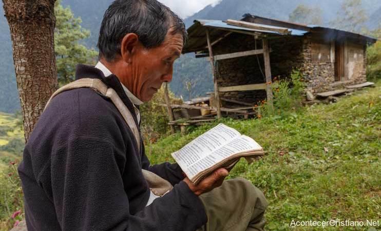 Hombre asiático leyendo la Biblia en el campo