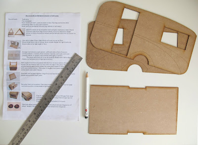 Modern dolls' house miniature retro caravan kit bottom and sides laid out on a work table, with instructions.