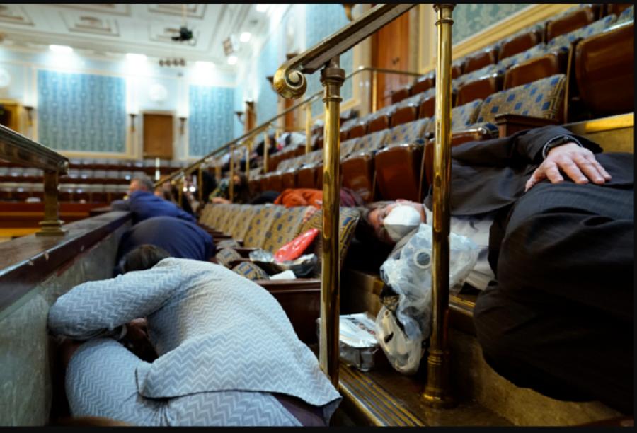 La gente se refugia en la galería de la Cámara mientras los manifestantes intentan irrumpir en la Cámara de la Cámara en el Capitolio de los Estados Unidos el miércoles 6 de enero de 2021 en Washington / VOA