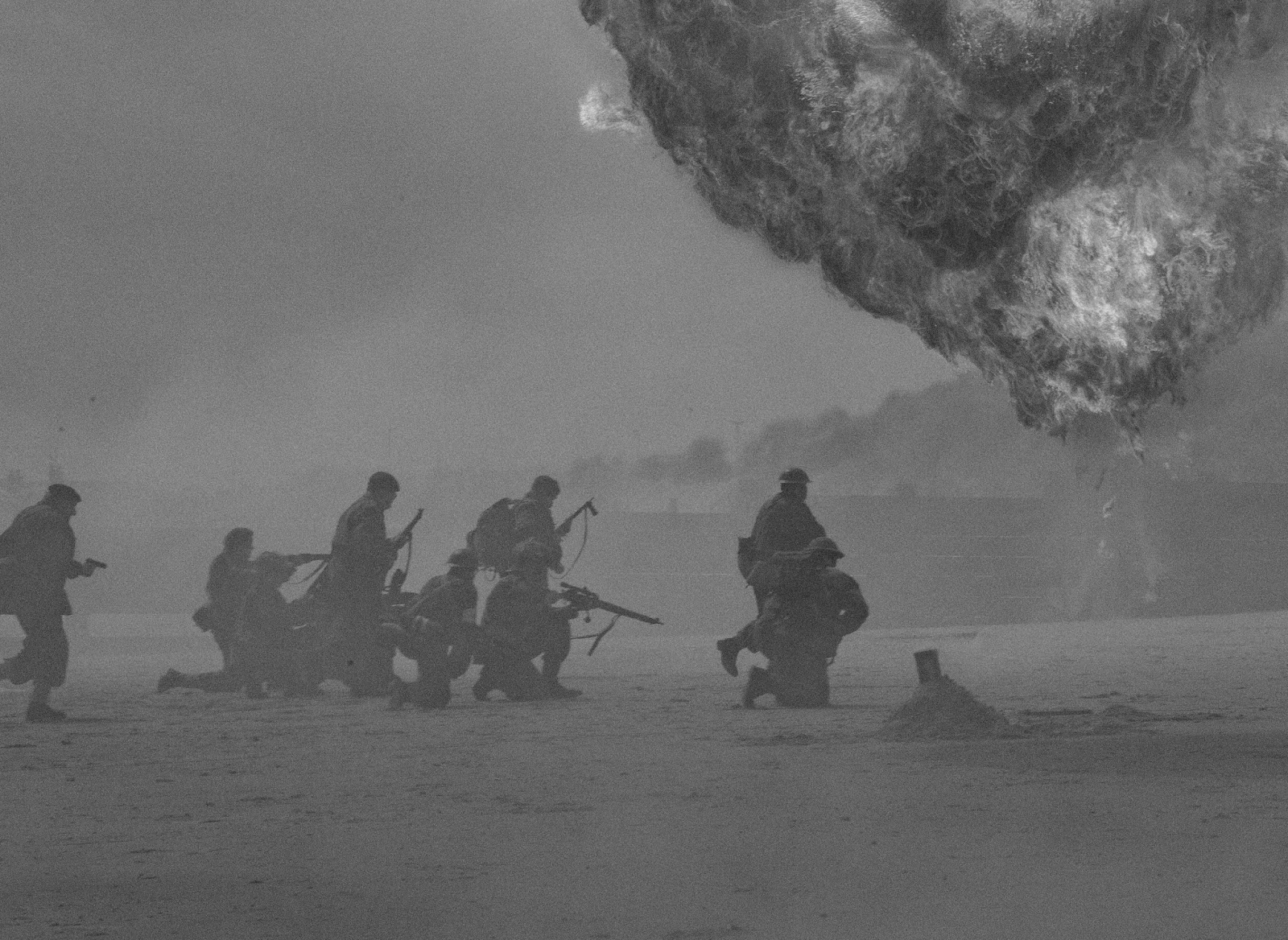a group of soldiers storm a beach with explosions in the background for blog post about war movies in the pacfic theater of world war 2