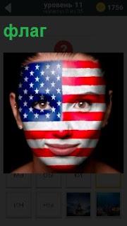 Лицо девушки разукрашено в национальные цвета флага. Волосы гладко зачесаны назад, губы сомкнуты