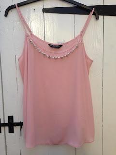 a baby pink cami top with gem detailing around the neckline