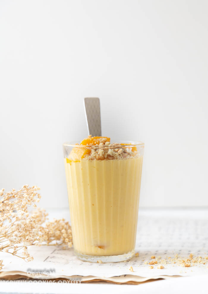 Mango cheesecale lassi served in a glass topped it up with fresh mango pieces and digestive biscuits crumbs with a spoon.