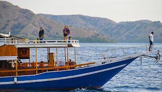 Wisatawan berpose di atas perahu pinisi di sekitar Pulau Kalong, Nusa Tenggara Timur, 2 Juli 2021. Kapal pinisi menjadi pilihan terbaik untuk menuju objek wisata Pulau Komodo, Pantai Pink, Manta Point, Pulau Padar, dan Pulau Kelor. Wisatawan yang ingin melakukan perjalanan singkat ke beberapa destinasi wisata disana dapat juga bisa menggunakan kapal cep. ANTARA FOTO/Rivan Awal Lingga