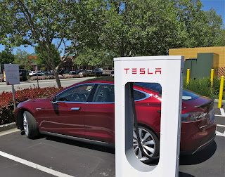 A red tesla model s charges at a tesla charging station