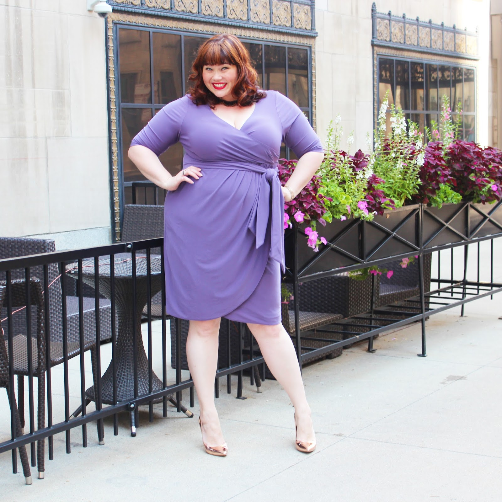 Plus Size Blogger Amber from Style Plus Curves models a lavender purple plus size faux wrap dress from Kiyonna