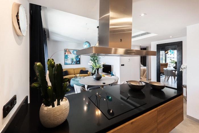 Cocina abierta al salón con isla. Encimera negra y mobliario en color roble