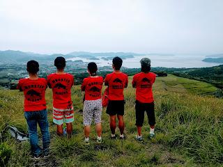 山頂から海を見渡すメンバーの後姿