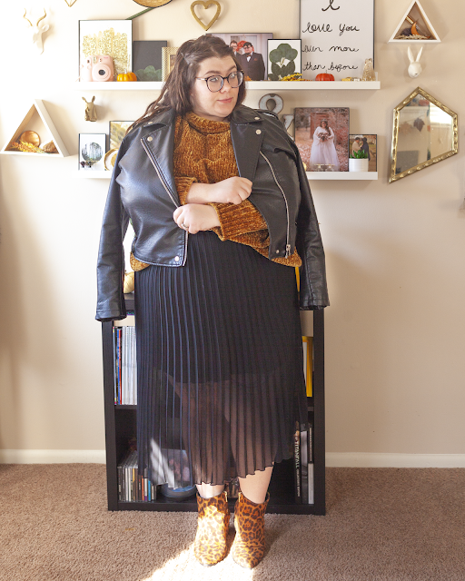 An outfit consisting of a black faux leather moto jacket draped over the the shoulders, a dark ochre yellow chenille sweater half tucked into a black pleated midi skirt and brown animal print boots.