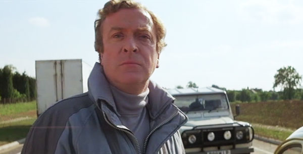 Michael Caine standing in front of a Land Rover