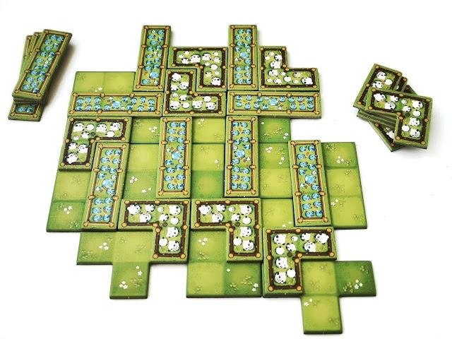 na zdjęciu plansza a na niej ułożone częśc kafli graczy w taki sposób, że gracze odgrodzili sobie fragmenty pastwiska aby ułożyć tam później swoje kafle i uniemożliwić to przeciwnikowi