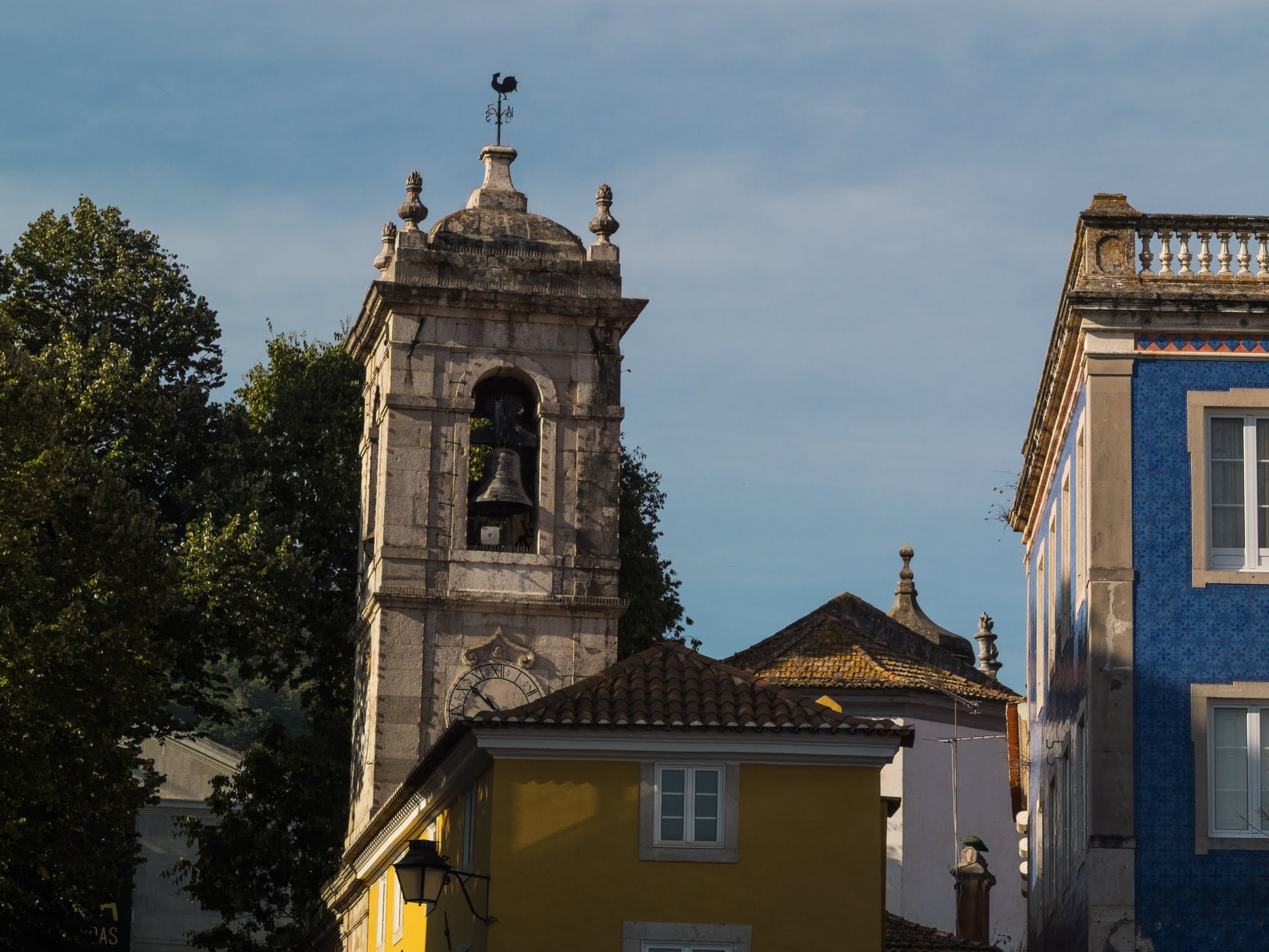 Colourful buildings in front of the Sao Martinho Church bell tower in Sintra, Portugal.