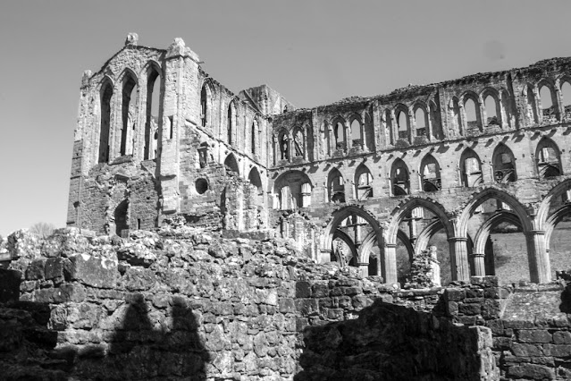 Monochrome photo, looking up at the main ruin from a courtyard below. The sky and the shadows make it look quite atmospheric and eerie.