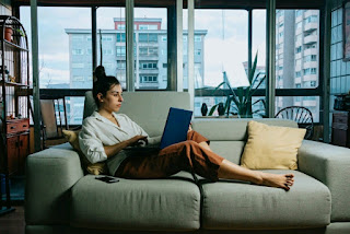 A woman using a laptop while lying on an extended sofa.