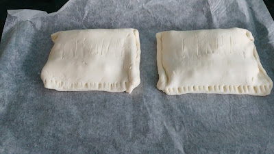 Two uncooked pies sitting on baking paper side by side